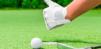 closeup hand in a white glove and a ball near the hole